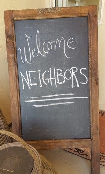 "Chalk board sign stating ""Welcome Neighbors"" for neighborhood party."